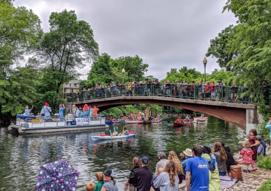 Spectators watch from a river bank as a pontoon and canoes travel down the Yahara River