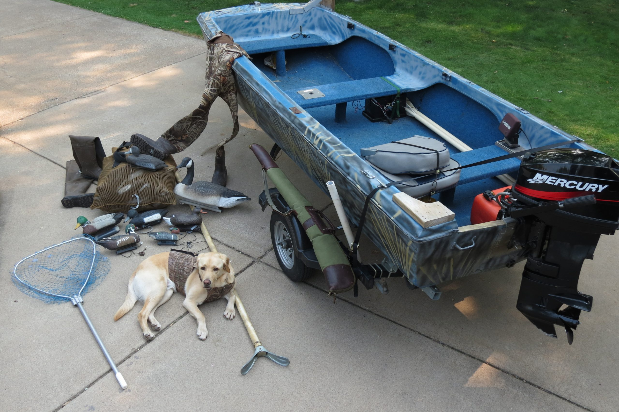 Photo of a duck hunting boat with a dog and hunting gear